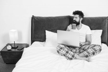 Hipster bearded guy pajamas freelance worker. Remote work concept. Social networks internet addiction. Online shopping. Man surfing internet or work online. Just woke up and already at work 版權商用圖片