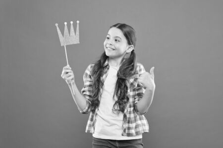 That pride of hers. Cute small girl holding prop crown with pride on orange background. Adorable little princess feeling great pride of crown on stick. Pride and joy