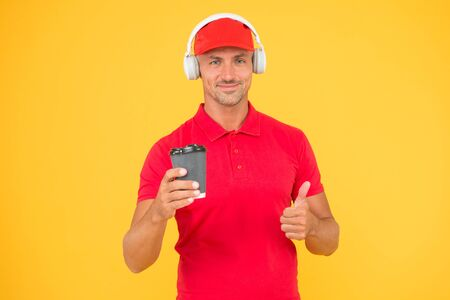 Here is your coffee. Cafe operator cashier hold coffee cup. Have a nice day. Coffee to go. Cafe stuff red uniform with cap serving coffee yellow background. Man recommend to try drink. Hot beverage