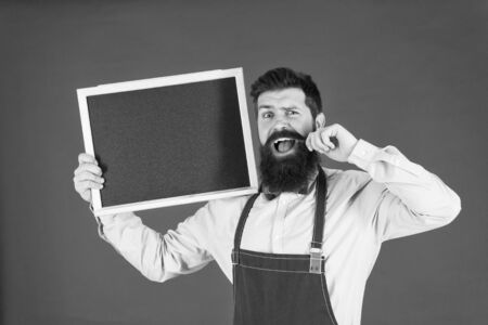 Happy hours bar. Man bearded bartender or cook in apron hold blank chalkboard. Price list concept. Hipster bartender show blackboard copy space. Hipster restaurant staff. Hipster informing you Stockfoto