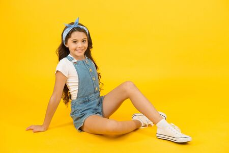 A fashion statement. Fashion look of small vogue model. Adorable girl in fashion wear on yellow background. Fashionable little child relax in casual fashion. Gorgeous and beautiful