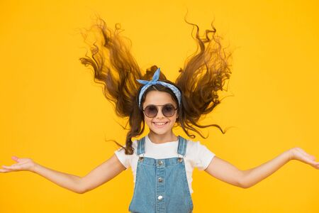 Feeling good fabulous hair. Adorable girl with curly hair waving on yellow background. Little hair model with fashion look. Small cute girl with long brunette hair. Hairdressers or beauty salon