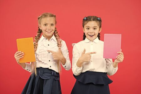Passionate about books. Happy little girls pointing at books on red background. Cute small children smiling with encyclopedia or hand books. Educational books for pupils and students