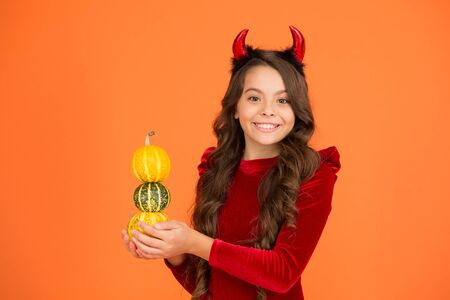 Decorations for holidays. Grocery shop. Autumn holidays. Pumpkins traditional attribute of fall holidays. Happy holidays. Cute child celebrate Halloween. Having fun. Small imp girl play with pumpkins Banco de Imagens