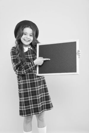 Back to school. Small school child pointing finger at blank blackboard on yellow background. Cute little schoolgirl with chalkboard on school day. Adorable pupil having school lesson, copy space