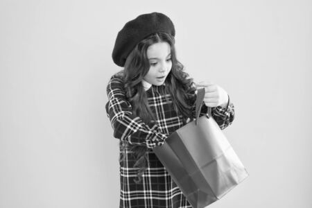 Just a minute of surprise. Little girl looking for surprise gift on yellow background. Small child holding shopping bag with surprise. Adorable shopper with surprise emotion on face