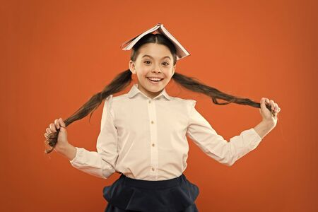 Let your hair speak for itself. Cute little girl holding long brunette hair on orange background. Small school child with book on head wearing hair in ponytails. Hair styling and haircare for school Stock Photo