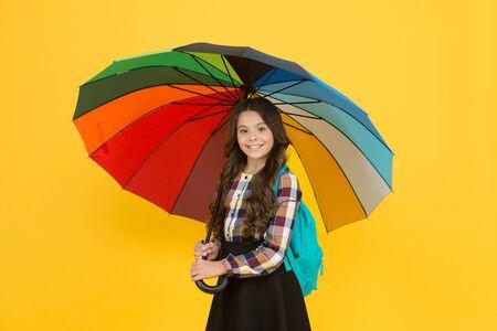 Rainy weather with proper garments. On way to school. Cheerful smiling schoolgirl. Rainy day fun. Happy walk under umbrella. Enjoy rain concept. Kid girl happy hold colorful rainbow umbrella