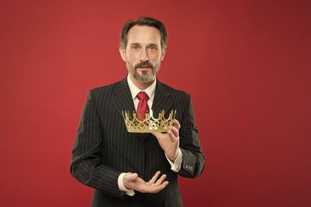 Reaching the height of luxury and elegance. Mature man holding luxury crown jewel on red background. Successful businessman with luxury and classy look. Luxury and prestige Stok Fotoğraf