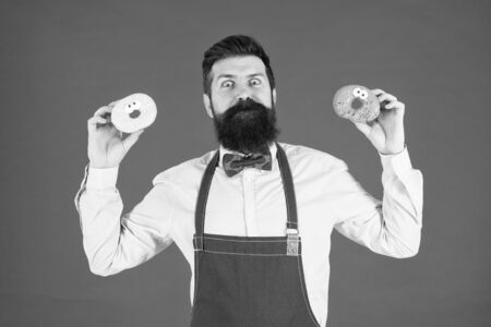 Catering bakery products to you. Bearded man holding ring donuts in bakery shop. Professional baker with glazed bakery food on red background. The perfect doughnuts from our bakery