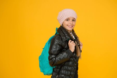 Backpack for keeping belongings secure on the go. Little child wear school backpack on yellow background. Small girl travelling with backpack on autumn holidays. Her backpack is as practical as cute