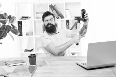 Stressful job at call center. Man bearded guy headphones office hammer smartphone. Spoiled communication. Failed mobile negotiations. Most annoying thing about work in call center. Incoming call Stockfoto