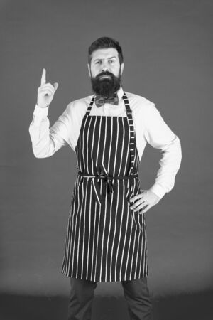 I know everything about cooking. Bearded man chef cooking. Hipster cooking home or restaurant. Modern cafe concept. Cooking modern meals. Man with beard cook hipster apron. Chef cook red background Stockfoto