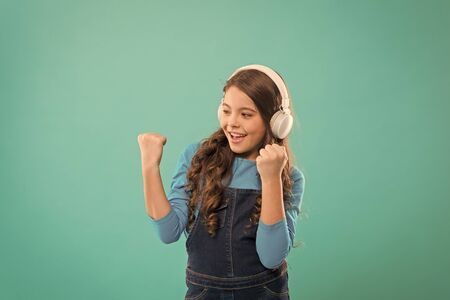 She isnt nothing but a winner. Happy little child making winner gesture on blue background. Small winner listening to music in headphones. Excited winner or champion celebrating victory