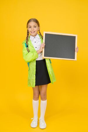Placement of ad. Little child hold blank blackboard for information on yellow background. Small schoolgirl smile with tidy information board. Sharing happy information. Your information, copy space
