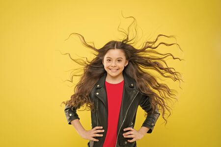 Hairdresser is a girls best friend. Cute little girl with long wavy hair happy smiling on yellow background. Kids hairdresser. Hairdresser salon for children. My hairdresser is good with her hands Stock Photo