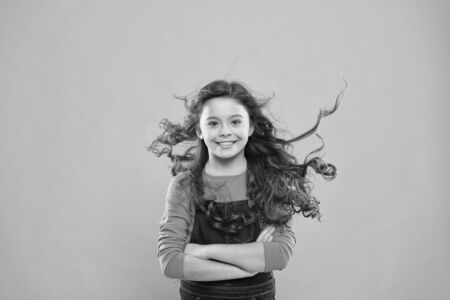 Just amazing. Happy child with long curly hair on blue background. Small child smiling with beauty look. Brunette female child with long wavy hairstyle. Cute little child wearing casual style Stock Photo