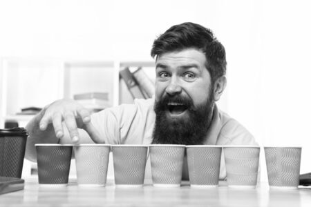Pick one. Diversity and recycling. Eco paper cup. Coffee to go paper cup. How many cups per day. Choose from alternatives. Man bearded choosing one of lot colorful paper cups. Alternative concept Stockfoto