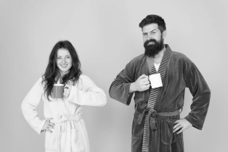 Every morning begins with coffee. Couple in bathrobes with mugs. Man with beard and sleepy woman enjoy morning coffee or tea. Guy in bath clothes hold tea coffee. Start new day. Breakfast concept Reklamní fotografie