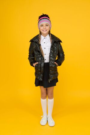Be stylish on chilly days. Stylish schoolgirl keep hands in pockets in casual outerwear. Little child with stylish autumn look on yellow background. Stylish and comfortable Stock Photo