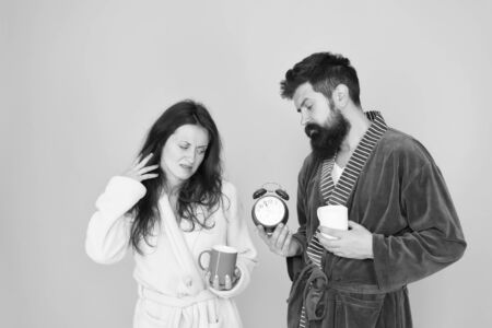Its coffee time. Couple in bathrobes with mugs. Man with beard and sleepy woman enjoy morning coffee or tea. Guy in bath clothes hold tea coffee. Breakfast concept. Every morning begins with coffee Reklamní fotografie