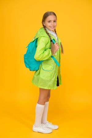 On your back and ready to go to school. Little school girl wear cute raincoat on yellow background. Adorable kid with school backpack on rainy day. Small child back to school in autumn