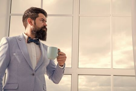 modern businessman. thoughtful bearded man drink coffee. businessman in modern formal outfit. modern life. business man at window. future success. morning inspiration. copy space. modern office