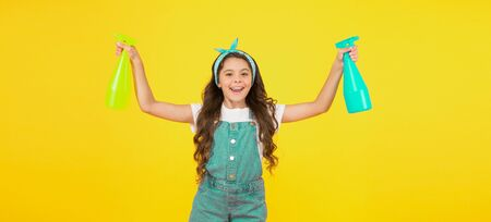 Miss clean. Clean home is happy home. Happy little girl hold spray bottles on yellow background. Small child keep house clean. Cleaning dirt. Household work. All surfaces clean at all times