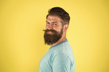 Bring your hair to the next level. Happy hipster with long beard and stylish hair on yellow background. Bearded man with unshaven face hair. Brutal guy with shaped beard and mustache hair Reklamní fotografie