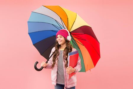 Every day fun. Child enjoying simple things. Entertain yourself. Fun concept. Feeling good. Girl having fun walking wireless headphones under colorful umbrella. Fall leisure. Music always with me