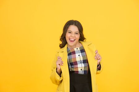 Yellow mood. Fancy child smiling face on yellow background. Yellow color. Girl fashionable cute model wear yellow wool coat. Personal styling and bespoke tailoring. Feeling cozy and comfortable