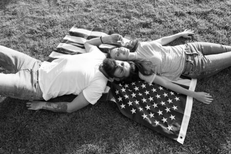 4th of July. American tradition. History of America. American patriotic people. American couple relaxing on USA flag outdoors. Independence day. National holiday. Bearded hipster and girl in love