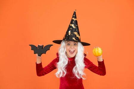 Halloween party. Small girl in black witch hat. Autumn holiday. Join celebration. Halloween attributes. Little child in witch costume. Magical spell. Small witch with white hair. Wizard or magician Stock Photo