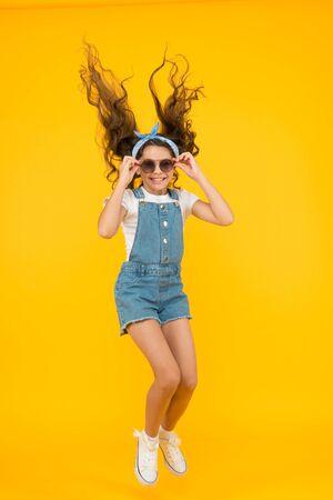Establezca un estado de ánimo verdaderamente enérgico y optimista. Niña enérgica con cabello largo morena saltando sobre fondo amarillo. El niño pequeño activo con aspecto lindo se siente enérgico. Estilo de moda enérgico