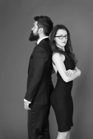 Man bearded hipster and woman in formal dress red background. Formal fashion and elegant clothes. Luxury fashion boutique. Fashion clothes shop. Official event. Couple man in tuxedo and elegant girl Stock fotó