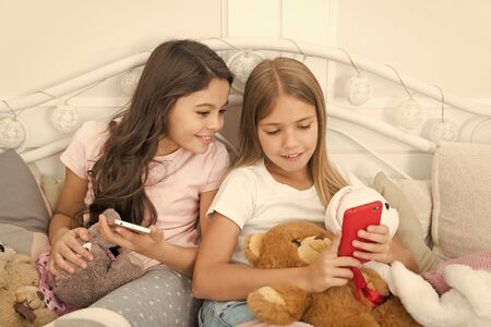 Sharing good news. Little girls use smartphone in bed. Ordering gifts for Christmas and New Year by phone. Happy little children with mobile phone. Merry Christmas and Happy New Year greetings 免版税图像