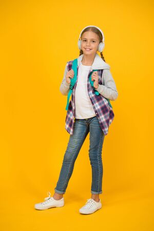 Happy carefree child. School and leisure. Modern education. Energetic cheerful teen listening music. Stylish schoolgirl going to school. Girl little fashionable girl carry backpack. School daily life 免版税图像