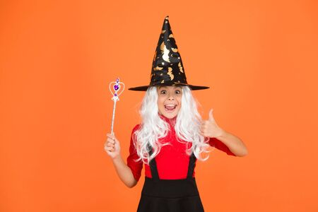 Having fun with magic. Little child in witch costume. Halloween party. Small girl in black witch hat. Autumn holiday. Join celebration. Magical spell. Small witch with white hair. Wizard with stick