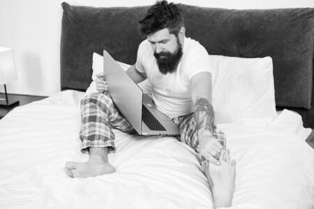 Checking messages. mature male with beard in pajama on bed. asleep and awake. energy and tiredness. businessman with computer. bearded man hipster work on laptop. brutal sleepy man in bedroom