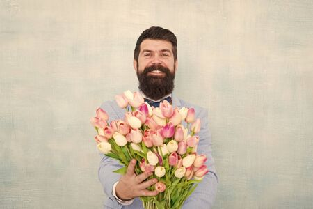 Gentleman romantic surprise for her. Flowers delivery. Gentleman romantic date. Birthday greetings. Best flowers for girlfriend. Spring holiday. Man bearded suit bow tie hold tulip flowers bouquet Stock fotó