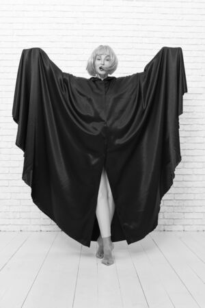 Being a real fun party girl. Playful woman having fun with crazy look on white brickwall. Sensual woman wearing yellow hair wig and black toga for fun. The fun has just begun Stockfoto