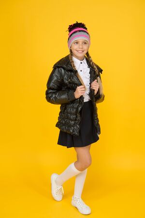 Keeping fashion and cosy. Little girl schoolchild in cozy fashion outfit on yellow background. Autumn look of small fashion model. Cold weather fashion for kids. Be cool in this luxurious coat
