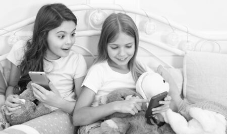 It cant be true. Happy little children with mobile phone. Merry Christmas and Happy New Year greetings. Little girls use smartphone in bed. Ordering gifts for Christmas and New Year by phone
