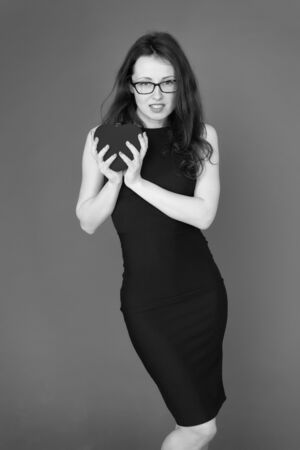 Happiness in her hands. Fall in love. Woman elegant black dress hold heart soft toy. Love from first sight. Woman stylish dress and eyeglasses hold symbol love. Romantic concept. Girl in love dating