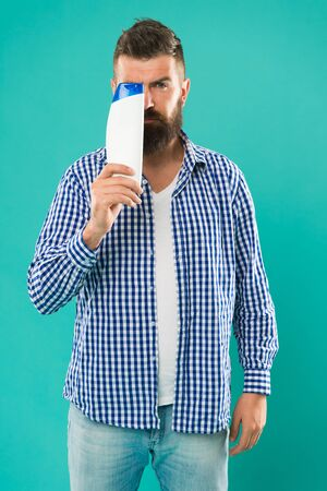 see the perfection. beard hair care grooming. male beauty. self hygiene. good morning. choose this shower gel. brutal hipster hold shampoo bottle. Bearded man with healthy hair. Cosmetic for spa bath Фото со стока