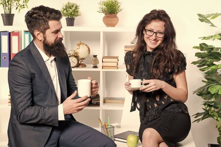 A working lunch meeting. Colleagues talking during work lunch. Sexy woman and bearded man enjoying lunch break in office. Company employees having tea or coffee for lunch