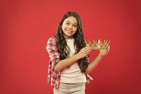 A very rich reward. Little girl holding crown reward on red background. Successfil small winner with precious reward for success. Winning valuable prize and reward