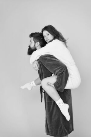 Reliable support. Handsome young man piggybacking beautiful woman. Couple in bathrobes having fun. Trust and support. True love. Lets stay at home. They are closest people. Support in any time Stok Fotoğraf