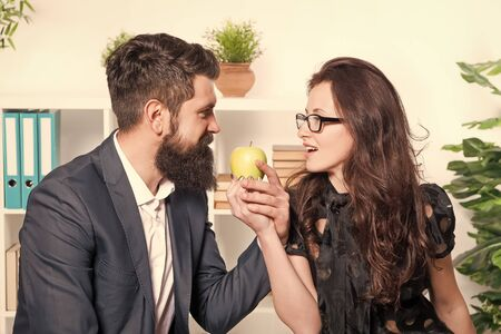 Apple is high in vitamin. Boss and sensual secretary holding vitamin fruit in office. Bearded man and sexy woman with healthy vitamin snack at work. Vitamin food actually works Stockfoto