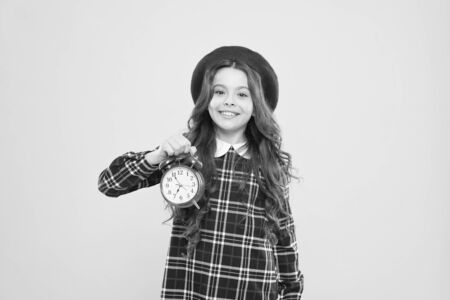 Putting her alarm clock on. Happy little girl holding alarm clock on yellow background. Small child smiling with mechanical clock. Wakeup clock